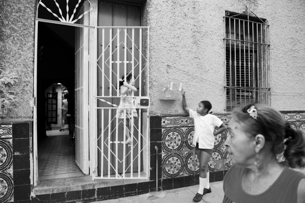 Caged bird on the street of tiled row houses - La Habana
