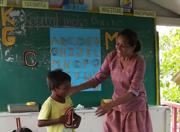 A Bajau learner joyously learns from his teacher: a common scene at the boat classroom in Buggoc, Zamboanga – the program that will be supported by proceeds from Manulife's GradMaker app.