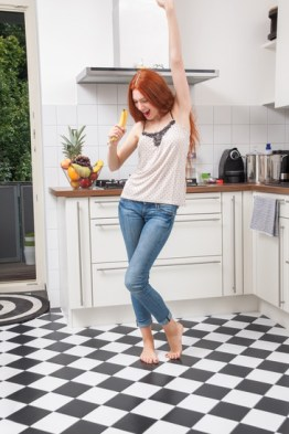 Happy Pretty Young Woman Holding a Banana Fruit, Dancing Alone at the Kitchen Inside the Home.