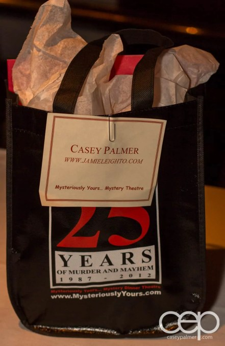 The take-home bag emblazoned with the Mysteriously Yours... Mystery Dinner Theatre 25th Anniversary celebration logo
