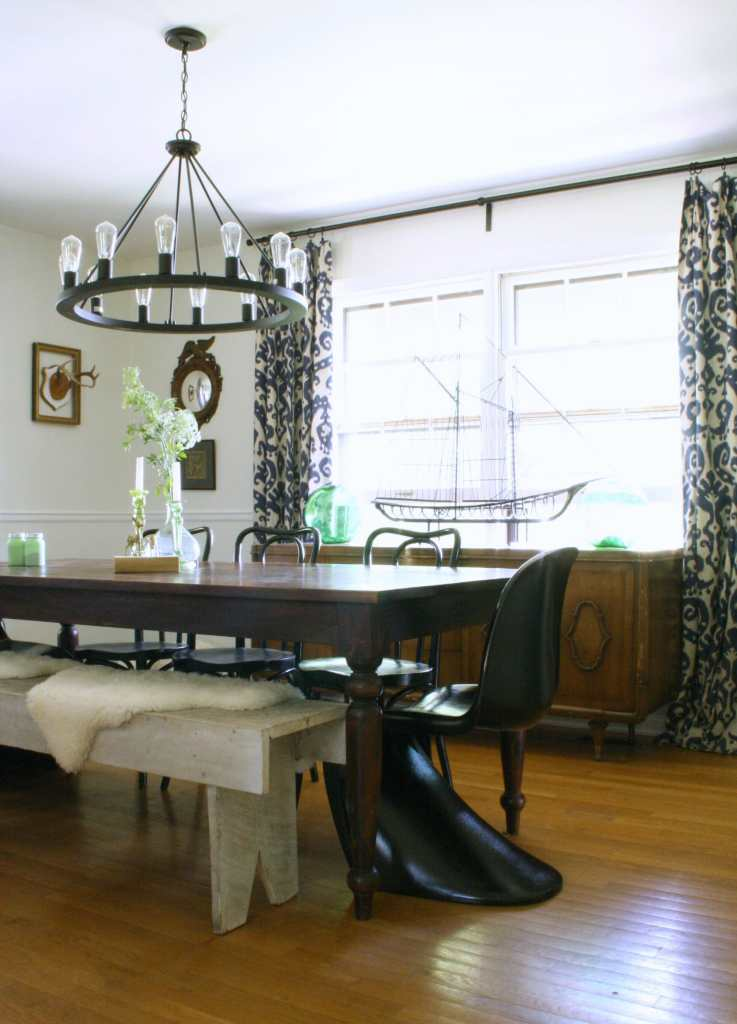 Eclectic White, Black, And Navy Dining Room with Bentwood chairs, Panton Chairs, and a bench