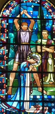 detail of a stained glass window of the martyrdom of Saint Eugenia; date unknown, artist unknown; church of Notre-Dame de Clignancourt, Paris, France; phtographed on 28 August 2010 by GFreihalter; swiped from Wikimedia Commons