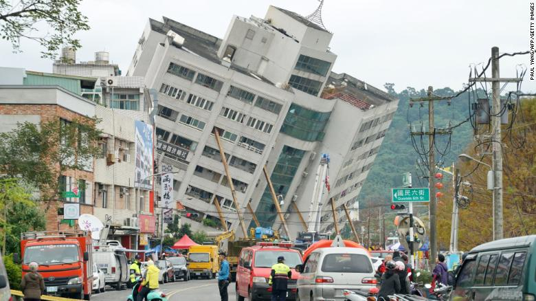 Emergency workers block off a street in Hualien, Taiwan, where a building threatens to collapse.