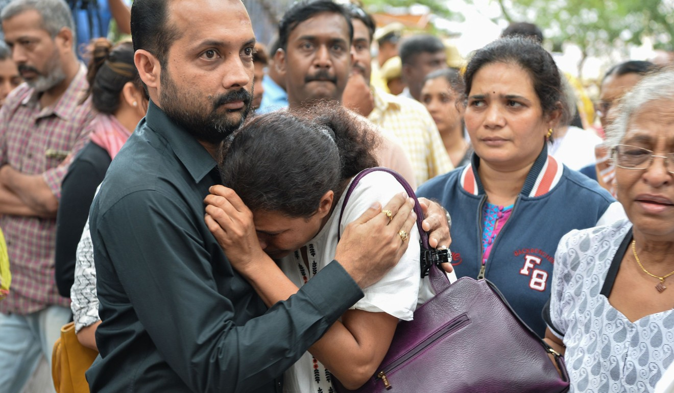 Kavitha Lankesh is consoled by a relative as the body of her sister Indian journalist Gauri Lankesh is brought to the Ravindra Kalakshetra cultural centre in Bangalore. Photo: AFP
