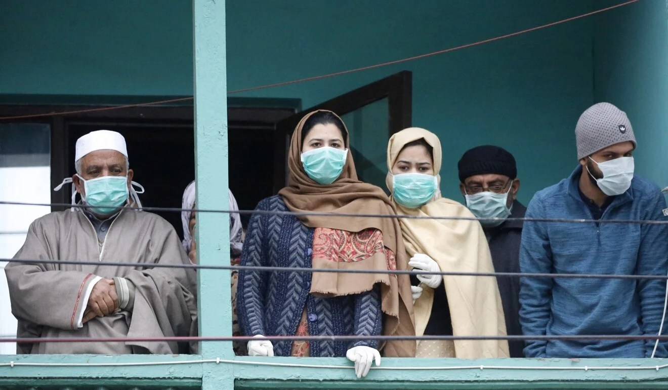 A group of people who returned to Kashmir from the Gulf look on from a hotel in Srinagar, where they have been kept in quarantine. Photo: EPA-EFE