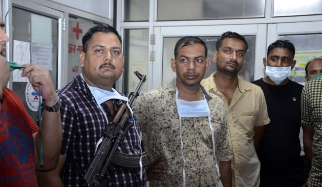 Police officers stand guard at a hospital where the body of Vikas Dubey is being kept. Photo: AP