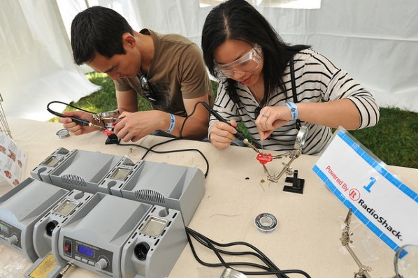 Maker Faire attendees learning how to solder.