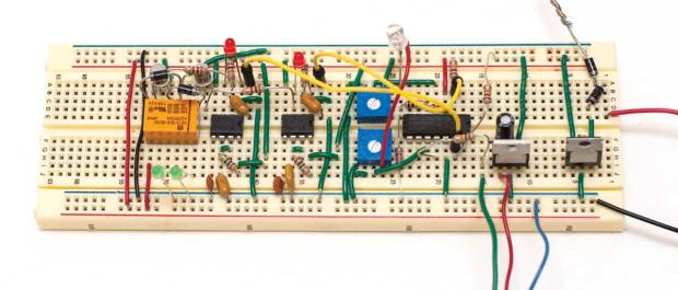 A complete breadboarded circuit showing the orange relay with input transistors and 2 green test LEDs, two 555 timers with red test LEDs, blue trimmer potentiometers, LM339 quad comparator chip, and voltage regulators for 3.3VDC and 5VDC.