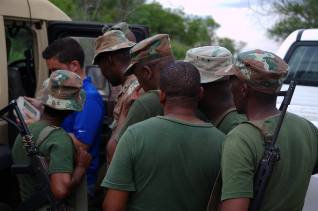 SANDF troops huddle around John Glezellis from Aurora Flight Sciences to see real time surveillance footage of the Mozambique border.