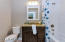 Hall bathroom with tub and white beveled subway tile. Granite vanities and Kohler toilet and sink package.
