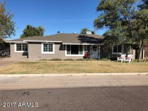 Picturesque front curb appeal with large grassy lawn and mature trees.