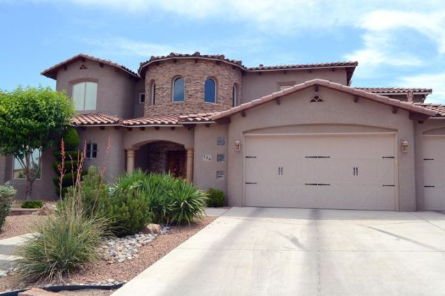 Stunning front with xeriscape for easy maintenance and custom garage doors.