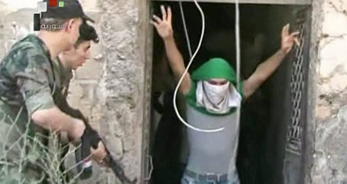 This still image from Syrian state TV video, shows a young man with his face covered surrendering to government forces, in Aleppo, Syria, Saturday, July 30, 2016