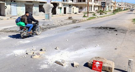 Men ride a motorbike past a hazard sign at a site hit by an airstrike on Tuesday in the town of Khan Sheikhoun in rebel-held Idlib, Syria April 5, 2017