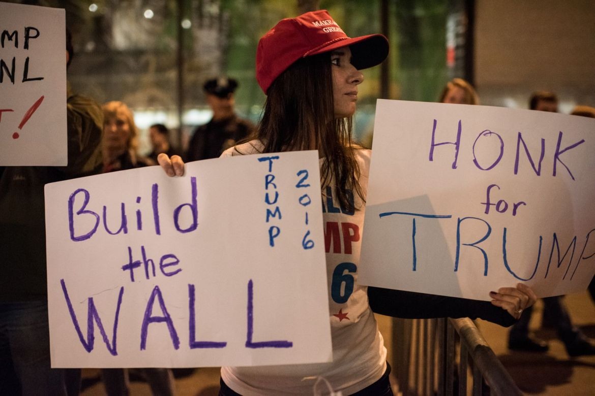 A Trump supporter carries a sign saying
