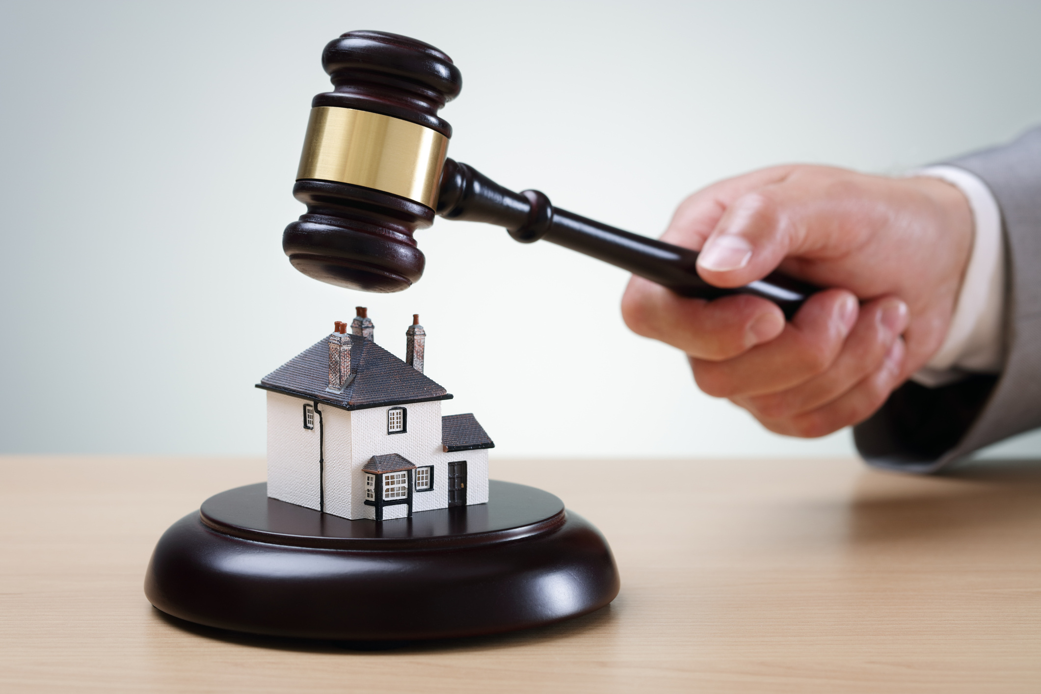 Bidding on a home, gavel and house concept for home ownership, buying, selling or foreclosure