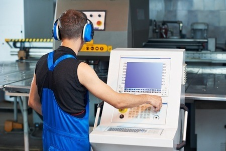 Man in uniform operating manufacturing equipment on a C-N-C turning machine