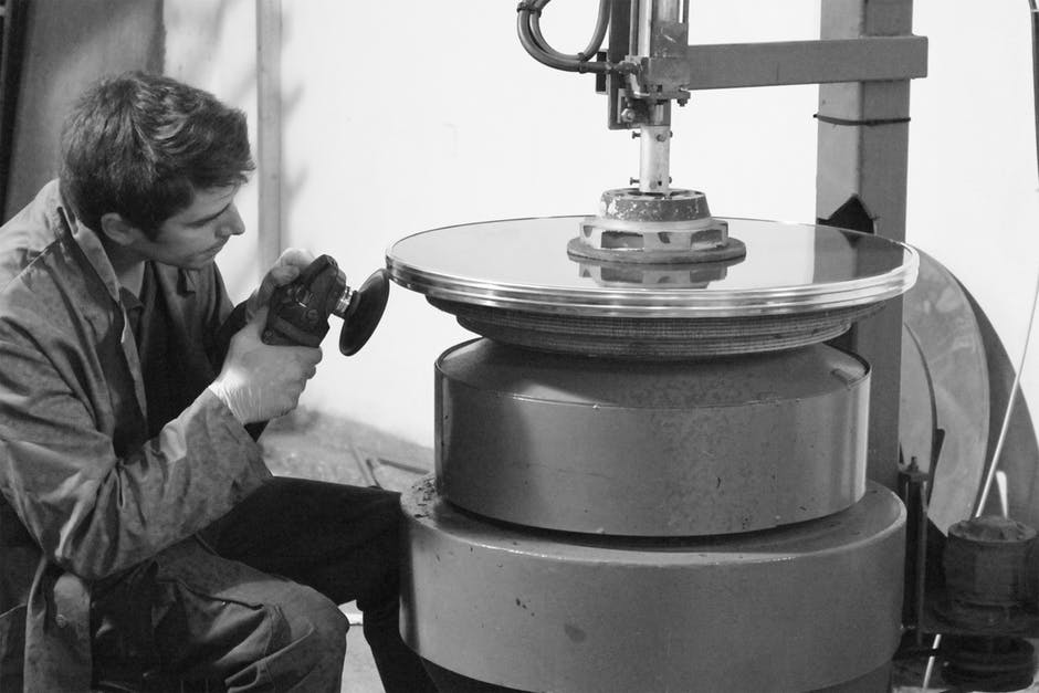 an image of a man working at a vertical lathe he is sitting in front of a large piece of metal being formed on the lathe and he has a hand grinder in his hands it it a black an white photo