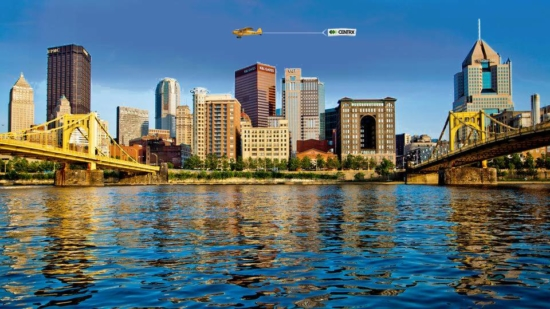 An image of the Pittsburgh Skyline on a sunny day showing the 3 rivers, not a cloud in the sky with a small yellow Plane Towing A Banner with the centrx logo on it advertising