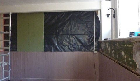 The back wall of the snug getting its waterproof membrane and proper plasterboard