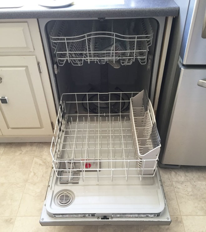 A view of the dishwasher showing the interior with the bottom tray pulled out.