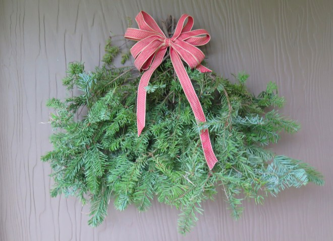 Finished evergreen spray with a ribbon bow hanging on our front door.