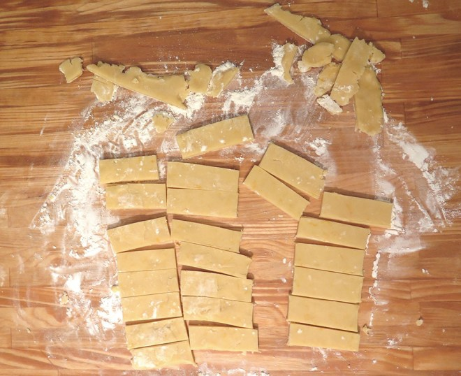 Cutting shortbread into rectangles and trimming the edges.