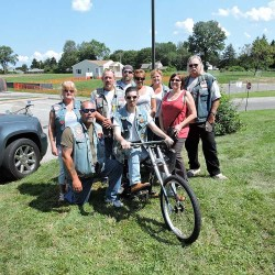 Siting atop his new Schwinn Stingray bicycle, Brookhaven resident Jonathan Berkheimer poses with Ann Skulski (far right, red shirt), and members of various motorcycle clubs that contributed to the cost of the bike.