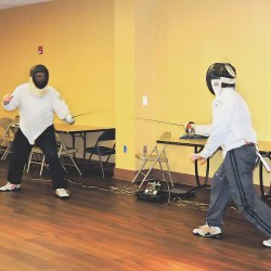 Brian Kroon and his son, Matthew, of the Wallingford Swarthmore Panthers Fencing Club, participate in a demonstration.