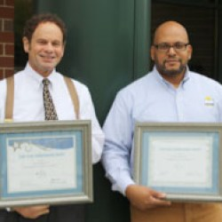 Chester Housing Authority Executive Director Steven A. Fischer (left) and Director of Housing Operations Norman D. Wise proudly display HAI Group awards for safe properties.