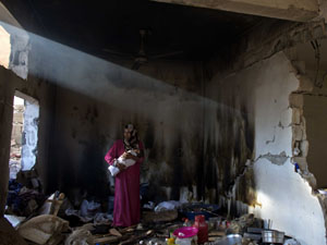 Palestinian mother and her baby in her home, still heavily damaged from the Gaza attack in 2014. Photograph: Levine/SIPA/Rex