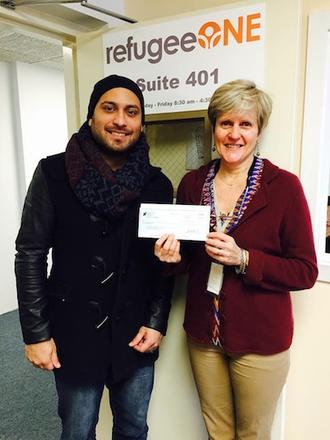NEIU Social Work student presents fundraising check to RefugeeOne representative. Feb. 2015