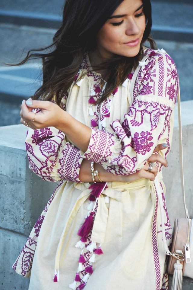 Carolina Hellal of Chic Talk wearing a Chicwish embroidered dress, H&M beige crossbody bag, Burgundy strap sandals, and Kendra Scott gold bracelets