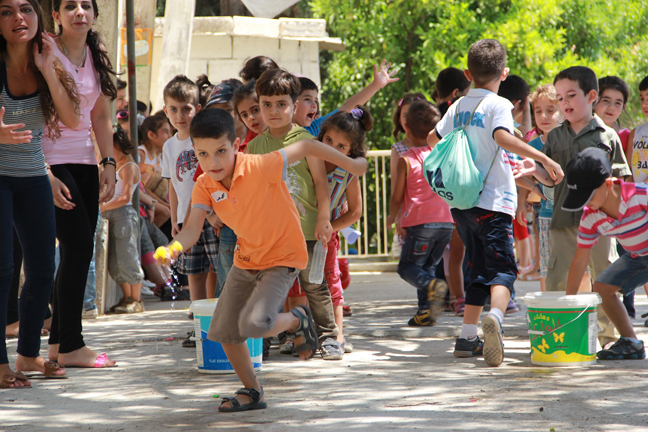 Children play together during a psychosocial activity at a UNICEF-supported centre. © UNICEF Syria/2013/Hassoun