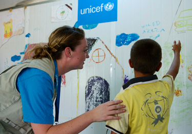 Ahmad, with UNICEF Communication Officer Melanie Sharpe at the camp. He is in the constant care of social workers. He attends youth-friendly spaces and is enrolled to go back to school this month. © UNICEF Jordan/Noorani