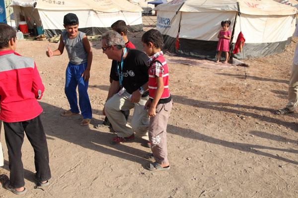 UNICEF Emergency Coordinator Jorge Caravotta plays marbles with children in Kawergosk refugee camp in northern Iraq. ©UNICEF/ Iraq-2013/Niles
