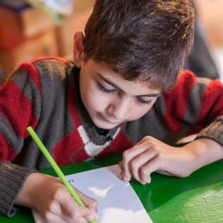 Moaaz practices writing the alphabet