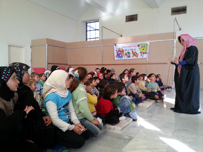 A hygiene promoter leads a session explaining the importance of hand washing, brushing teeth, and washing food. The children, aged between six and 15, have been displaced from their homes by the conflict and live in shelters in Tartous. © UNICEF/Syria-2014/Youngmeyer