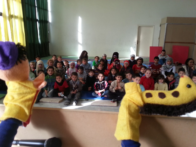 A puppeteer conveys hygiene messages through storytelling. The plot involves a doctor trying to find out whether the giraffe is ill due to a hygiene-related issue. © UNICEF/Syria-2014/Youngmeyer