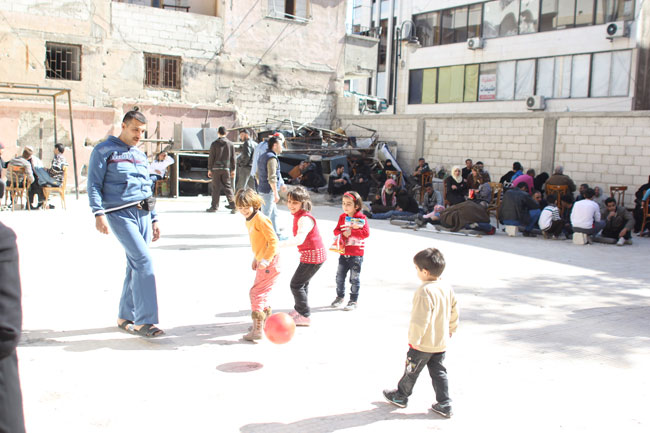 Abu Ibrahim kicks a ball with his children at the Al Andalous detention facility where he is being held for security clearance. He was just evacuated from the besieged Old City of Homs after an 18-month separation from his family. ©UNICEF/Syria-2014/Rashidi