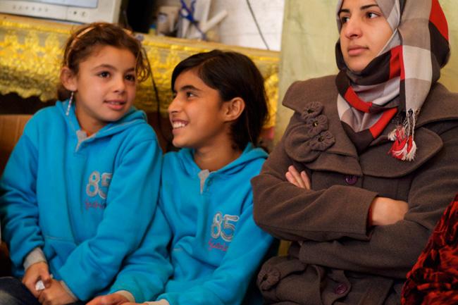 هدى البالغة من العمر 18 عاماً (يمين) تجلس مع أشقائها في خيمتهم في المخيم غير الرسمي في لبنان