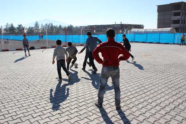 مجموعة من الأطفال يلعبون كرة القدم بعد انتهاء دوامهم في المدرسة