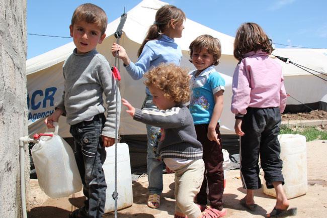 أطفال في مخيم دوميز للاجئين السوريين بشمال العراق يملؤون أوعية مائية