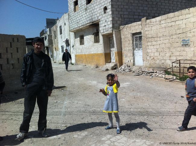 أطفال من دوما يلوحون إلى القافلة الأممية. هذه هي المرة الأولى التي تم فيها تسليم المساعدات لهم منذ عامين