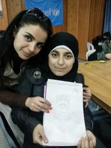 Thora, 18, and Rana, a Project Manager on the programme, hold up a picture drawn by Thora