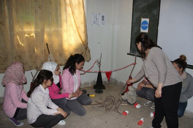 Students watch a simulation exercise on signs and clues for unexploded ordnance. © UNICEF/Syria-2014/Tiku