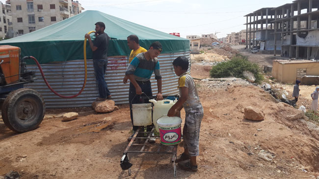 Two children load water containers onto a makeshift cart to take back to their family. UNICEF is providing water tanks as well as pre-fabricated toilets. © UNICEF Syria/2014/Kumar Tiku