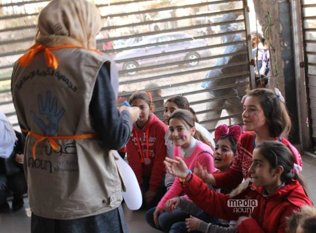 Young volunteer works with a group of young IDP girls at one of Aoun/UNICEF supported open day's activities sessions in Al Enshaat Area in Homs. This session reached 389 children including 209 girls   ©UNICEF/Syria/2015/Aoun/Ghadeer Qara Bolad