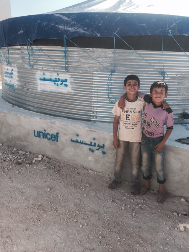 ©UNICEF Syria/2015. Two children pose happily in front of a newly installed Oxfam tank in an IDP shelter in Harim district of the governorate of Idleb. After months of deliberations, UNICEF installed 7 water tanks in areas with high concentration of internally displaced people (IDPs), including Atmeh and Qah camps along the Turkish boarders. The water tanks, each with a capacity of 45.000 Litres will provide more than 28.000 people with a stable access to clean drinking water.