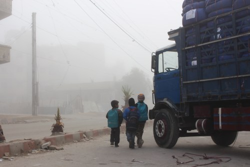 © UNICEF Syrian Arab Republic/2016/ElOuerchefani Morning has fallen, in the besieged area of Moadamiyeh. The last of the trucks of a long convoy of aid are being unloaded for this community in urgent need of essential supplies. Here, a few children are gathered near one of the trucks.